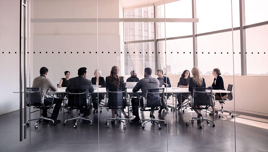 Photo of people sat round boardroom