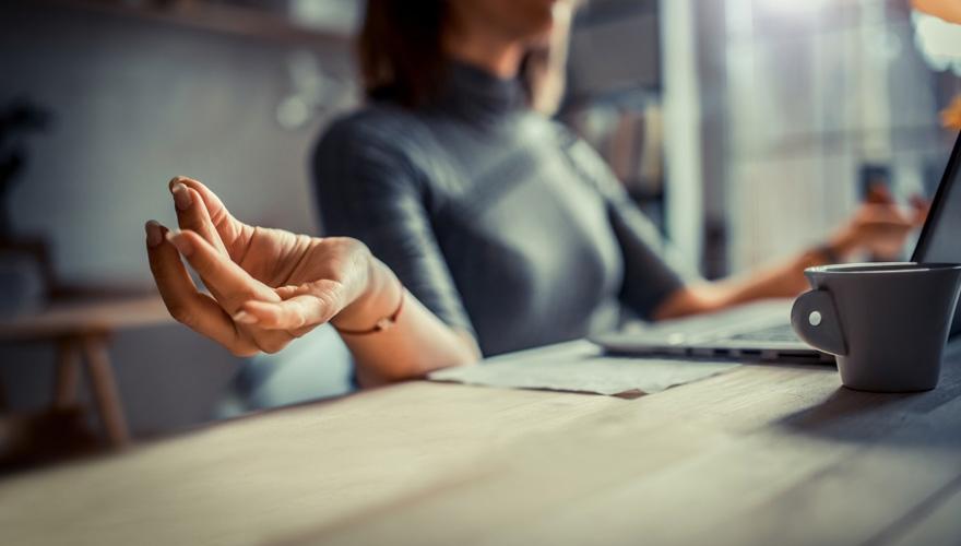 employee meditating at desk