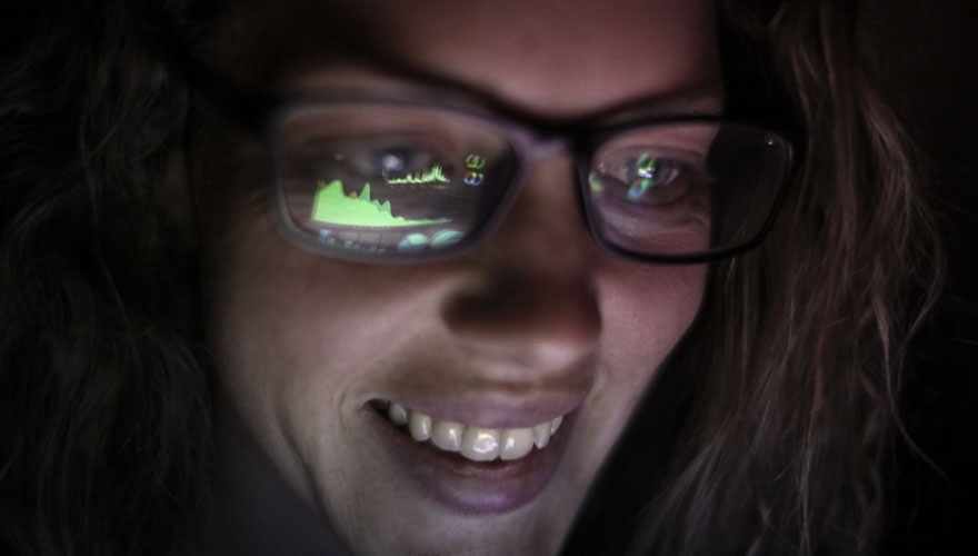 Lady in glasses looking at a screen reflected in her glasses image
